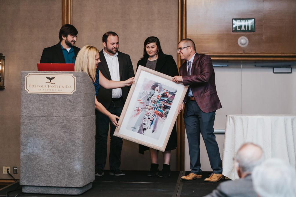Presenter handing art photo to recipients