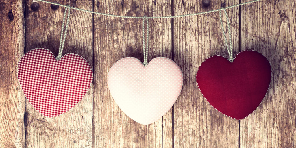 3 plush hearts hanging in front of wood background