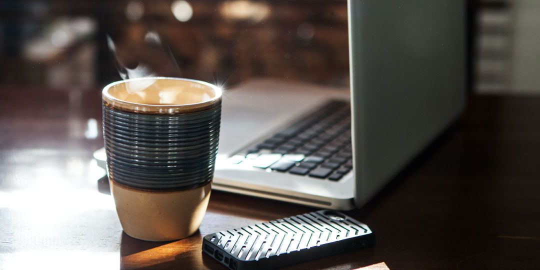 coffee mug by phone and laptop